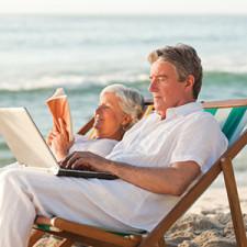 A senior man and woman recline on beach chairs reading books