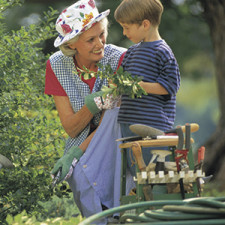 A grandmother and young boy work in a flower garden together
