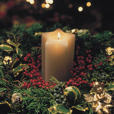 Lit candle in a Christmas wreath with holly