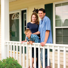 A young family standing on a porch of their home