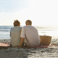 An older man and woman sitting on a picnic blanket watching the sunset on a beach