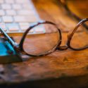 Closeup of glasses lying on a wooden desk next to a keyboard