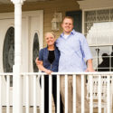 A young man and woman stand on the porch of their new home