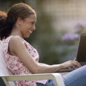 A young woman sits on a lawn chair and works on her computer