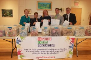 Volunteers with Cape Kid Meals pose for a photo with Lisa Oliver, President and CEO of The Cooperative Bank of Cape Cod, and Joe and Mike Thonus of ASAP Printing & Promotions. They stand behind table full of food ready to be put in the bags donated by The Cooperative Bank of Cape Cod.