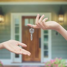 Image of a house key being passed from one hand to another in front of front door