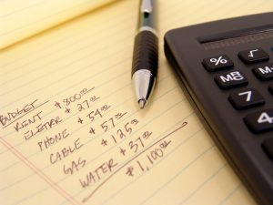 lined yellow pad paper with list of budget items. pen and calculator