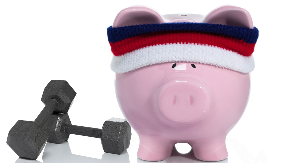 piggie bank with headband next to dumbells