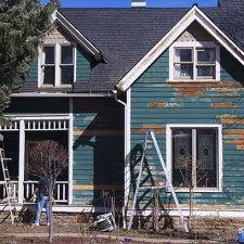 house with wood siding and chipped paint being repainted