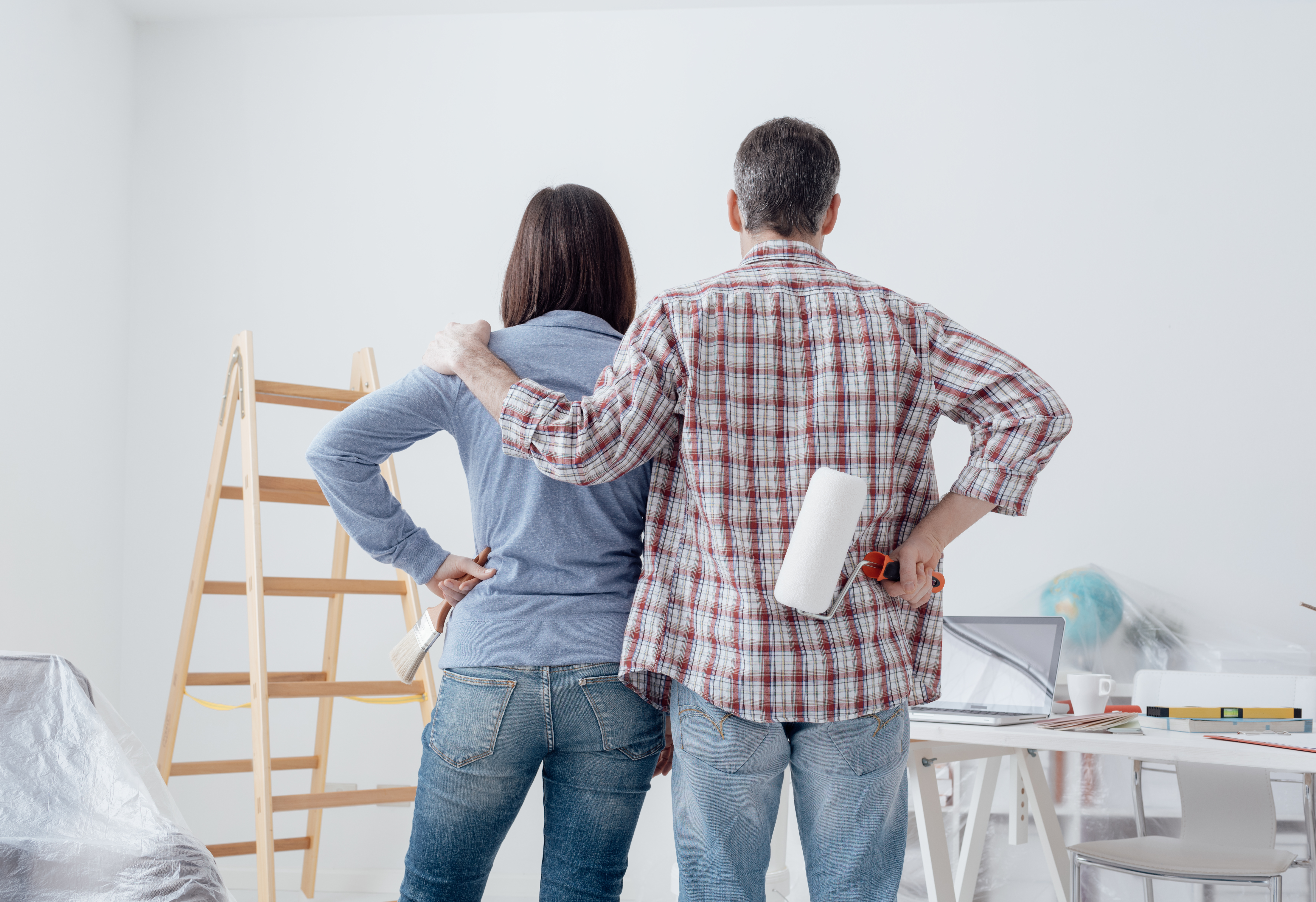 couple staring at their freshly painted room, back view: home renovation