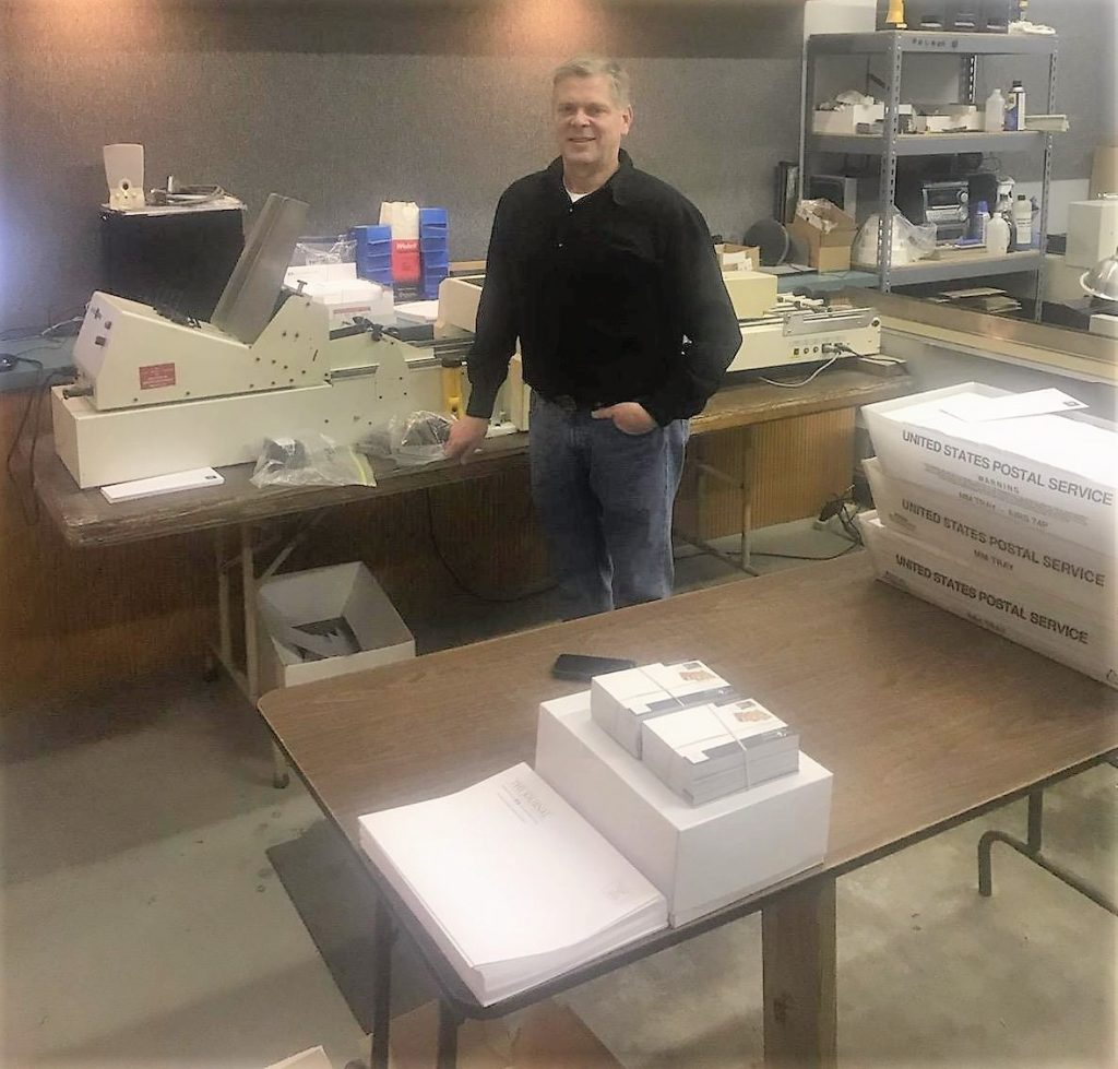 Photo of Ron Johnson, owner of Midnight Mail, standing in front of printing equipment