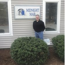 Midnight Mail owner, Ron Johnson, standing in front of business