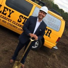 Mario Campos, owner of Stanley Steemer, standing in front of Stanley Steemer van