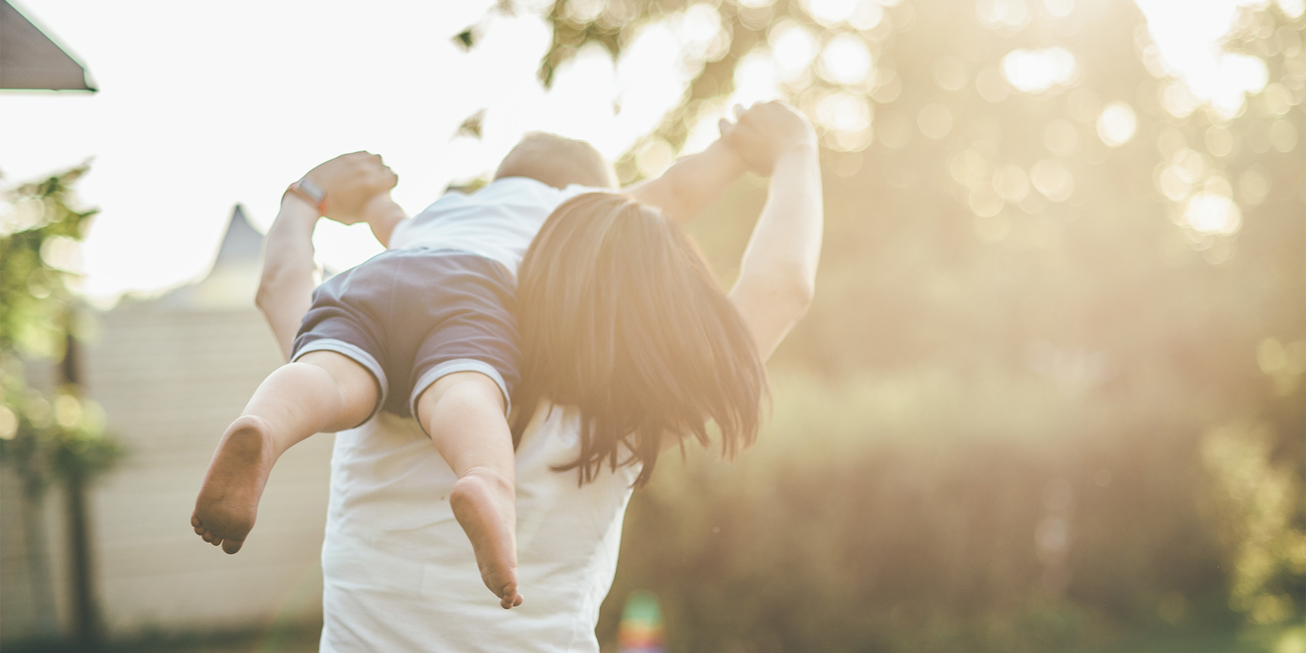 mom with child on her shoulders playing outside