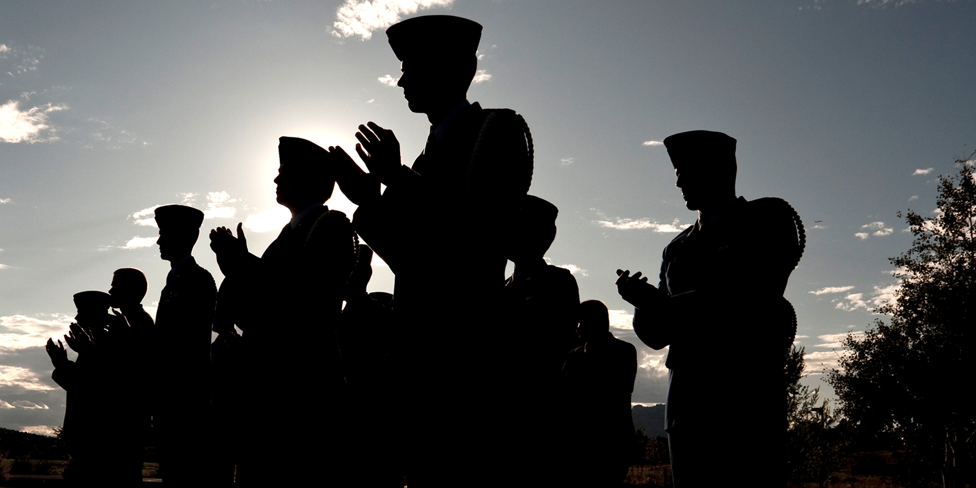 Soldiers standing together and clapping in shadow of sunny day