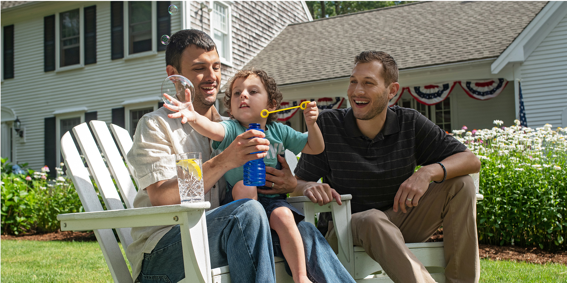 Two fathers sitting in white adirondack chairs outside with their son playing with bubbles