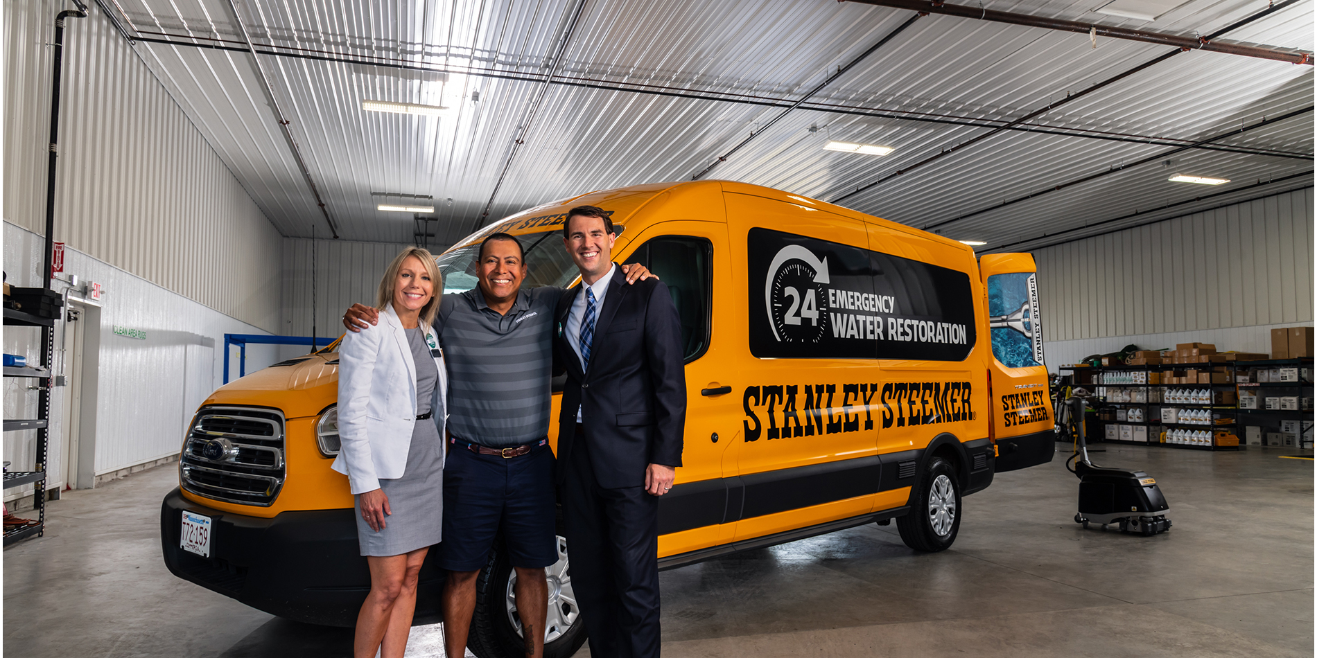The Coop's Betsy Hickey and Rob Carey with Mario Campos, owner of Stanley Steemer, standing in front of Stanley Steemer van