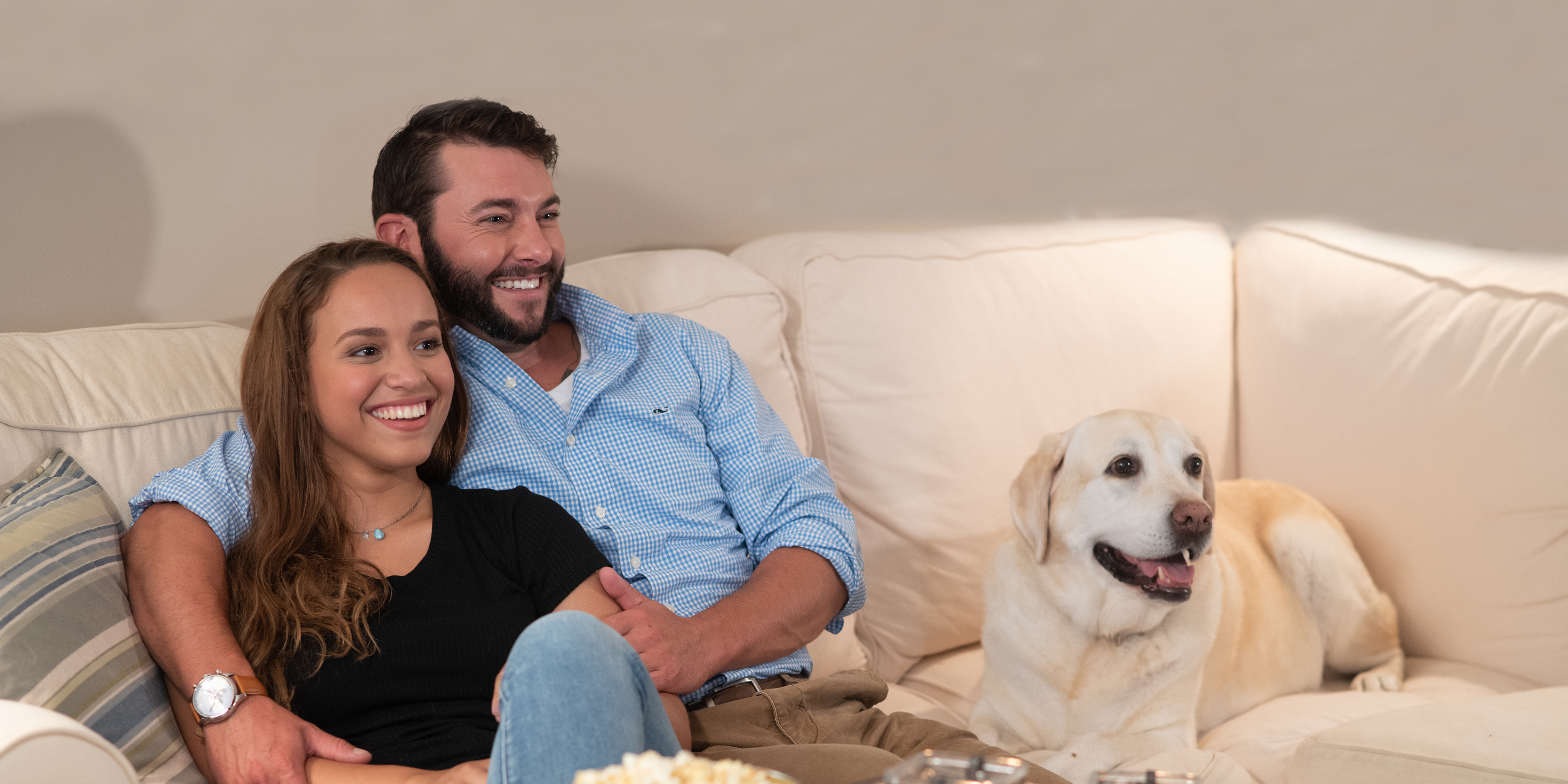 A young couple sits on the sofa with their pup.