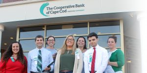 6 branch employees, part of the Bank's Tech Ambassador program, stand in front of The Coop's Admin & Operations Center