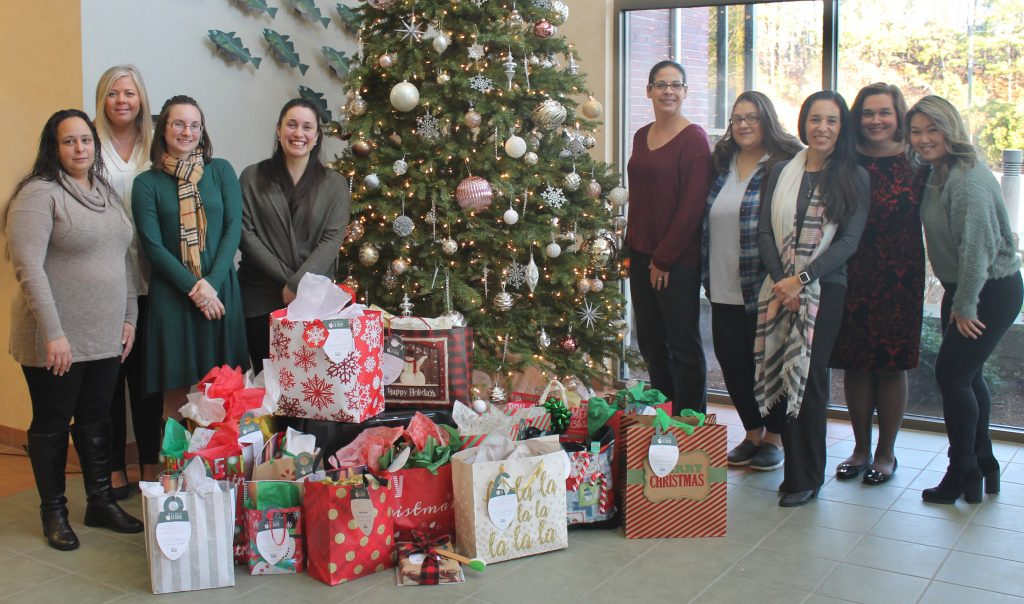 Coop employees gathered around decorated Christmas Tree surrounded by wrapped gifts for seniors in our community.