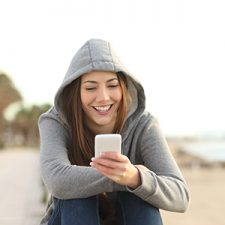 Dark haired woman in gray sweatshirt checks her phone while sitting on the beach