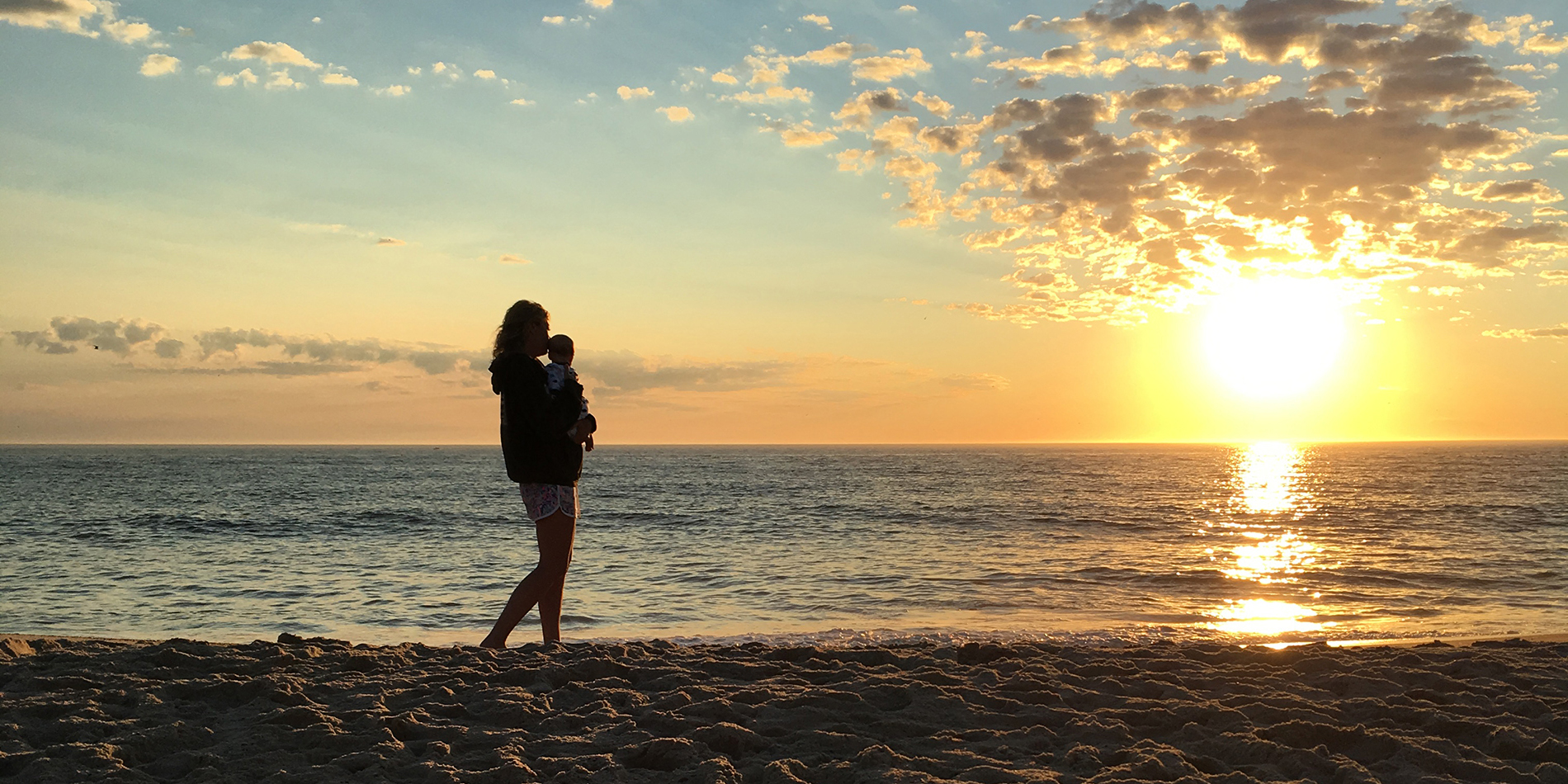 Mother holding baby while walking the beach at sunrise