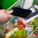 Mobile phone being used for paying for a cart of groceries