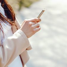 young long brown haired woman in a spring coat standing in a park texting on her mobile iphone