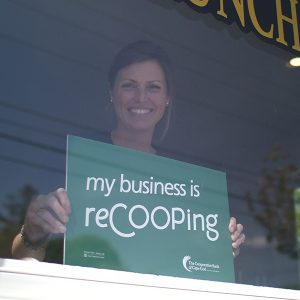 Kate, owner of Old Kings Coffee House, stands in the window of her business holding a 'my business is reCOOPing' sign