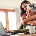 young woman hugging her grandmother before helping her with her finances on a laptop