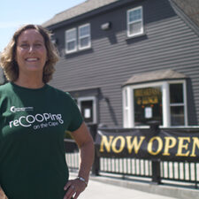 Coop Relationship Manager, Mary, wearing a ReCOOP tshirt, poses outside of small local business, Old Kings Coffeehouse