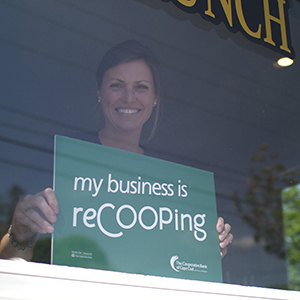 Local small business owner, Kate, hangs a 'My Business is ReCOOPing' sign in her business window