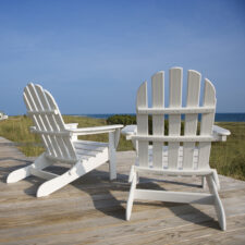 two white Adirondack chairs on dock of waterfront property