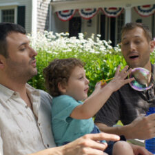 Image of family using bubbles with child